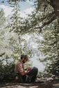 Side view of hiker sitting in camping seat at forest - CAVF31757