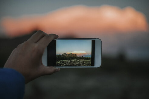 Cropped hand of woman photographing landscape with smart phone - CAVF31769