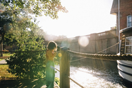 Girl standing by rope railing and looking at canal on sunny day - CAVF31772