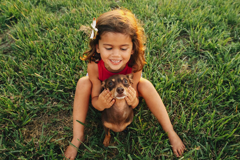 High angle view of happy girl with dog on field at park - CAVF31787