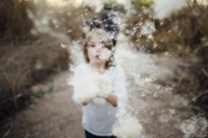 Girl blowing dandelion while standing on field - CAVF31835