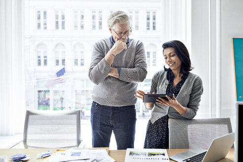 Businesswoman showing tablet computer to senior businessman while standing against window in creative office - CAVF32048
