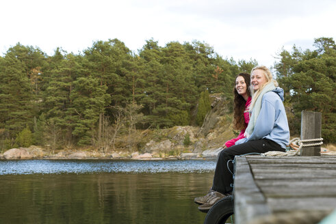 Teenage girl sitting with young woman on jetty - FOLF06040