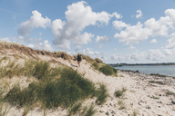 France, Brittany, Landeda, Dunes de Sainte-Marguerite, young woman walking in dune at the coast - GUSF00579