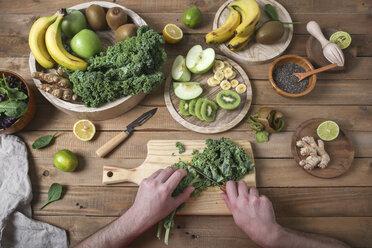 Man preparing green smoothie cutting kale - RTBF01124