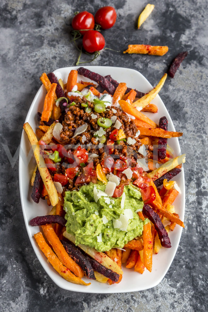 Vegetable fries with vegetarian bolognese, guacamole, yogurt dip, tomatoes, spring onions and parmesan on plate - SARF03641 - Sandra Roesch/Westend61