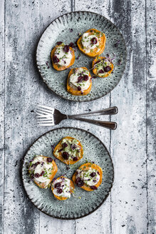 Slices of sweet potato with cream cheese, ramson cream, goat cheese, cress and cranberries - SARF03647