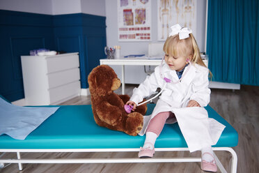 Girl with stethoscope examining teddy in medical practice - ABIF00218