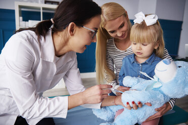 Doctor and girl with mother vaccinating teddy in medical practice - ABIF00224