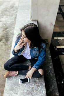 Young woman sitting on a wall smoking a cigarette - MGOF03748