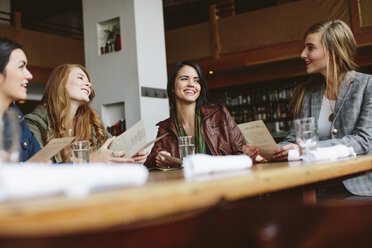 Happy female friends holding menu while talking at table in restaurant - CAVF32130