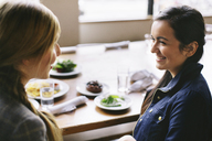 High angle view of happy female friends talking while sitting at table in restaurant - CAVF32133