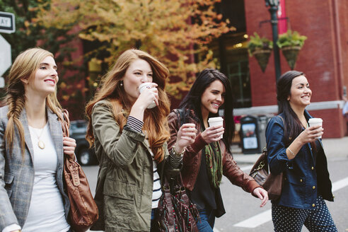 Happy female friends having coffee while walking on city street - CAVF32142