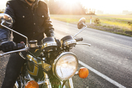 Midsection of biker sitting on motorcycle by road during sunny day - CAVF32160