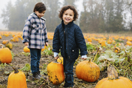 Portrait of happy boy carrying pumpkins while standing with brother at farm during winter - CAVF32172