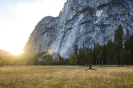 Cheerful woman jumping on grassy field at Yosemite National Park - CAVF32268