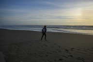 Rear view of man walking on sand at beach during sunset - CAVF32283