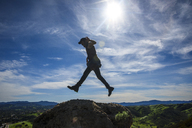 Side view of man jumping on rock formations against sky during sunny day - CAVF32292