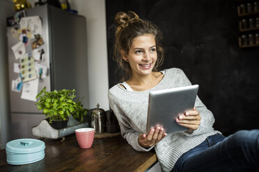 Smiling woman sitting at table holding tablet - PNEF00571
