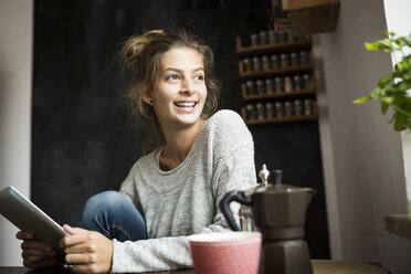Smiling woman sitting at table holding tablet - PNEF00574