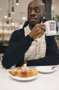 Man with croissant and cup of coffee in a cafe looking around - MAUF01359