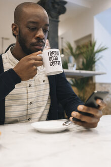 Man with cup of coffee in a cafe using cell phone - MAUF01362