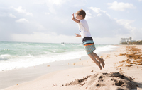 Side view of boy jumping at beach against cloudy sky - CAVF32374