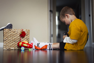 Side view of boy playing with toys while sitting on floor at home - CAVF32377