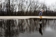Full length boy jumping in puddle against bare trees - CAVF32380