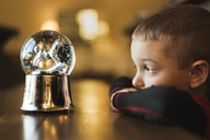 Side view of boy looking at snow globe - CAVF32386