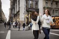 Happy female friends giving high five while walking on street - CAVF32578