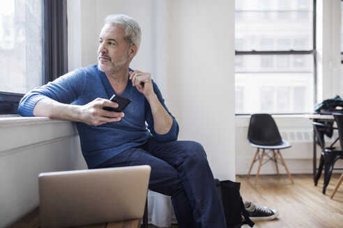 Thoughtful mature man holding smart phone while looking through window at home - CAVF32665