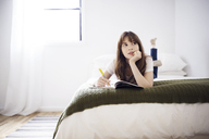 Thoughtful young woman looking away while studying on bed at home - CAVF32692
