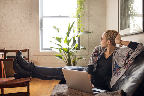Thoughtful woman looking away while using laptop on sofa at home - CAVF32749