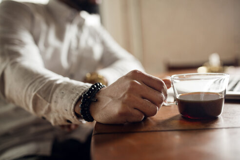 Midsection of man holding black coffee cup at table - CAVF32752