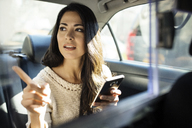 Young woman pointing while holding smart phone in taxi - CAVF32800