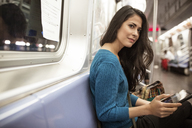 Young woman looking away while holding tablet computer in train - CAVF32815