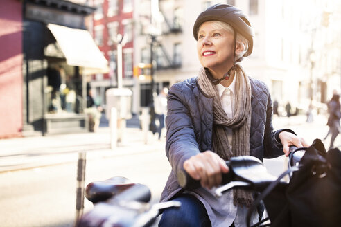 Thoughtful senior woman sitting on bicycle - CAVF32899