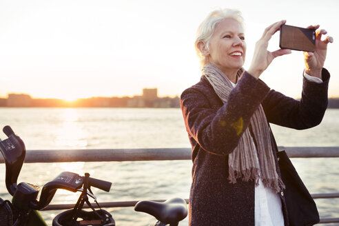 Happy senior woman photographing by sea during sunset - CAVF32911
