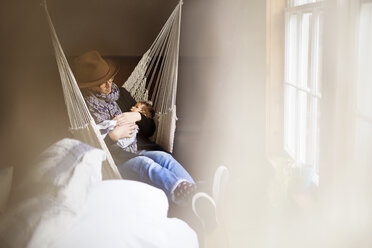 Loving mother sitting with baby boy on hammock at home - CAVF32917