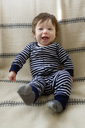 Overhead view of happy baby boy lying on bed at home - CAVF32926