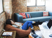 Woman talking on mobile phone while reclining on bean bag - CAVF33001