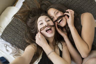 Overhead portrait of female friends making artificial mustache with hair - CAVF33013
