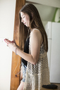 Side view of teenage girl using smart phone while standing by window at home - CAVF33016