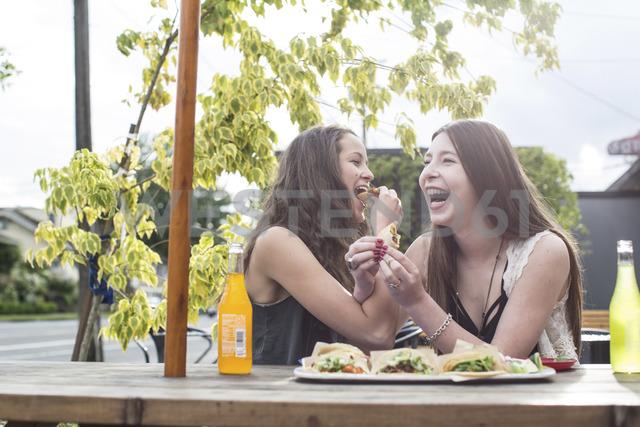 Cheerful female friends having food sidewalk cafe - CAVF33019 - Cavan Images/Westend61