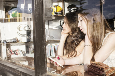 Female friends using smart phone while sitting in cafe seen through window - CAVF33025