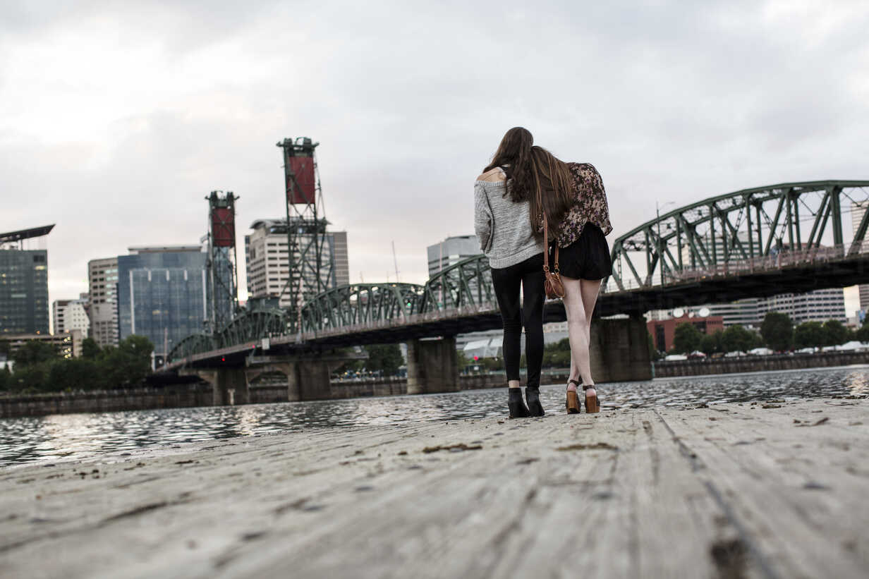 Rear view of female friends standing on pier against Burlington Northern Railroad Bridge 9.6 - CAVF33031 - Cavan Images/Westend61