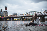 Female friends sitting on pier against Burlington Northern Railroad Bridge 9.6 - CAVF33037