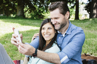 Happy couple taking selfie through mobile phone while sitting in park - CAVF33046