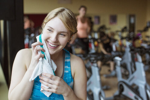 Smiling woman wiping sweat while standing in gym - CAVF33145